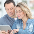 Couple using electronic tab in the street - Stock Photo