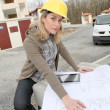 Woman engineer looking at plan on construction site — Stock Photo