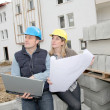 Architect and engineer looking at plan on construction site — Stock Photo #6698053