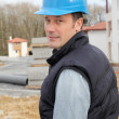 Stock Photo: Site supervisor with security helmet standing on construction site