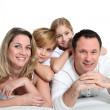 Happy family laying on bed — Stock Photo