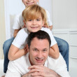 Portrait of father and children laying in sofa — Stock Photo