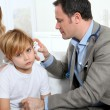 Doctor cheking little boy's ear infection — Stock Photo #6698297