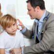Doctor cheking little boy's ear infection — Stock Photo
