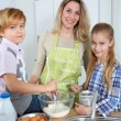 Mother and children in kitchen preparing cake — Stock Photo