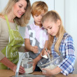 Mother and children in kitchen preparing cake — Stock Photo #6698431
