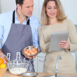Couple in kitchen looking at recipe on internet — Stock Photo