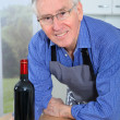 Elderly man holding bottle of red wine - Photo
