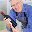Elderly man holding bottle of red wine - Stock Photo