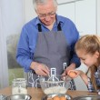 Grandfather with little girl preparing cake — Stock Photo