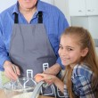 Grandfather with little girl preparing cake — Stock Photo #6698491