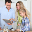 Stock Photo: Parents and daughter preparing meal in home kitchen