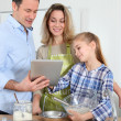 Parents and daughter preparing meal in home kitchen — Stock Photo #6698511