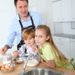Stock Photo: Father and children preparing pancakes