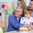 Little girl taking picture of family on birthday celebration - Foto Stock