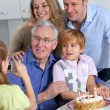 Stock Photo: Little girl taking picture of family on birthday celebration