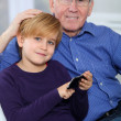 Old man with little boy playing video game on telephone — Stock Photo