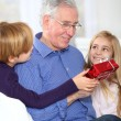 Kids giving birthday gift to their grandfather - Stock Photo
