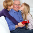 Kids giving birthday gift to their grandfather — Stock Photo