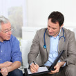 Doctor writing medical prescription to elderly man - Stock Photo