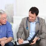 Doctor writing medical prescription to elderly man — Stock Photo
