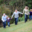 Family having fun running in park - Stock Photo