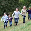 Family having fun running in park — Stock Photo