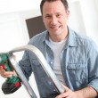 Closeup of smiling man with electric drill — Stock Photo #6698778
