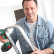 Closeup of smiling man with electric drill — Stock Photo