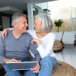 Happy senior couple connected on internet at home — Stock Photo