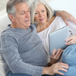 Senior couple sitting in sofa with electronic tablet — Stock Photo