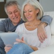 Senior couple sitting in sofa with electronic tablet — Stock Photo #6699195