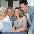Portrait of happy family sitting in sofa with electronic tablet — Stockfoto