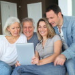 Foto de Stock  : Portrait of happy family sitting in sofa with electronic tablet