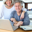 Senior couple surfing on internet at home - Stock fotografie