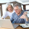 Senior couple making secured payment on internet - Stock fotografie