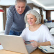 Stock Photo: Senior couple making secured payment on internet