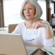 Senior woman at home in front of laptop computer — Stock Photo