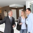 Real estate agent showing modern house to couple — Stock Photo #6699425