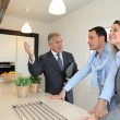 Real estate agent showing modern house to couple — Stock Photo #6699428