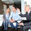 Stok fotoğraf: Couple with real-estate agent signing home investment contract