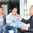 Real-estate agent giving house keys to young owners — Foto de Stock
