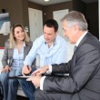 Couple with real-estate agent signing home investment contract — ストック写真
