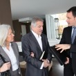 Senior couple visiting modern house with real-estate agent — Stock Photo