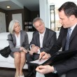 Senior couple signing financial contract for property purchase — Photo #6699478
