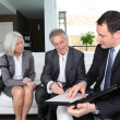 Senior couple signing financial contract for property purchase — Stock Photo