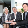 Stock Photo: Senior couple signing financial contract for property purchase