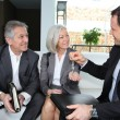 Real-estate agent giving house keys to senior couple — Stock Photo