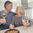 Royalty-Free Stock Photo: Senior couple drinking wine in home kitchen