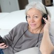 Senior woman listening to music with headphones — Stock Photo #6699753